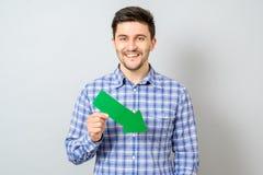 Homme avec la flèche verte indiquant la droite et vers le bas Photographie stock libre de droits