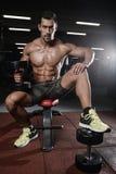 Homme avec la formation de poids dans le club de sport d'équipement de gymnase Photographie stock libre de droits