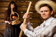 Homme avec la fourche et dans le chapeau, femme avec le panier Photo stock