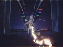 Homme avec la guirlande rougeoyante sous le pont photo libre de droits
