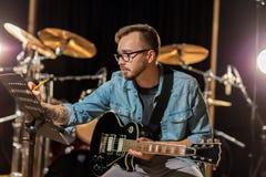 Homme avec la guitare écrivant au cahier de musique au studio image libre de droits