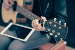 Homme avec la guitare électrique et le comprimé blanc Photos stock