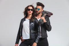 Homme avec la guitare électrique sur l'épaule tenant sa femme Photographie stock