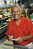 Homme avec la liste d'épicerie. Photos stock