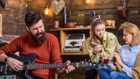 Homme avec la longue barbe touffue chantant passionément, concept de musique Filles buvant du thé ou du vin et appréciant de beau Images stock