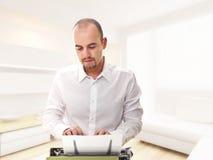 Homme avec la machine à écrire à la maison Image libre de droits