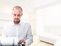 Homme avec la machine à écrire à la maison Photographie stock libre de droits