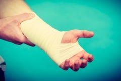 Homme avec la main bandée douloureuse Photo stock