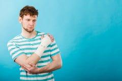 Homme avec la main bandée douloureuse Photographie stock libre de droits