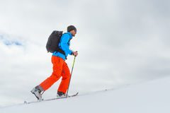 Homme avec la montée d'alpinisme de ski vers le sommet image libre de droits