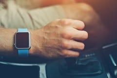 Homme avec la montre intelligente sur le poignet conduisant une voiture photo stock