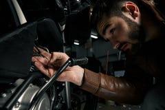 Homme avec la moto dans le garage Photos libres de droits