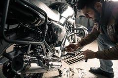 Homme avec la moto dans le garage Photo stock