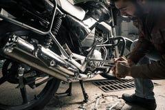 Homme avec la moto dans le garage Image stock