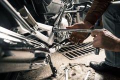 Homme avec la moto dans le garage Photos stock