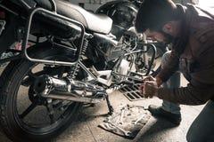 Homme avec la moto dans le garage Images stock