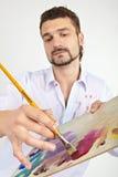 Homme avec la palette Concentré sur la main et la brosse photographie stock libre de droits