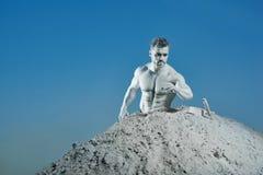 Homme avec la peau argentée parmi le sable faisant des gestes sur des instruments image libre de droits