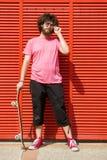 Homme avec la planche à roulettes sur le fond rouge photo libre de droits