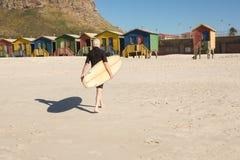 Homme avec la planche de surf marchant sur le sable contre des huttes de plage Image stock