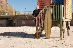 Homme avec la planche de surf se tenant sur des étapes sur la hutte de plage Photos stock