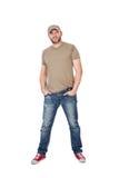 Homme avec la position de chapeau, de T-shirt et de jeans, d'isolement sur le blanc Photo libre de droits
