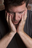 Homme avec la tête dans des mains Photographie stock libre de droits
