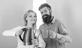 Homme avec la tasse et la femme avec la bouilloire électrique prête à boire du café de matin La première chose ils font chaque ma photographie stock libre de droits