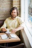 Homme avec la tasse et le livre de café dans le cafétéria Photo stock