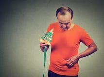 Homme avec la tranche de bande de mesure de pizza et d'abdomen de poids excessif Images stock
