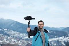 Homme avec la vidéo de enregistrement de stabilisateur et de caméra en montagnes L'hiver photographie stock libre de droits