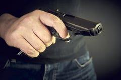 Homme avec la violence en caoutchouc d'attaque de pistolet d'arme à feu de main photographie stock libre de droits