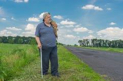 Homme avec le bâton de marche se tenant sur un bord de la route Images stock