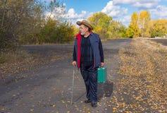 Homme avec le bâton de marche se tenant sur une route de campagne Photo libre de droits