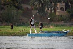 Homme avec le bateau en rivière Photos stock