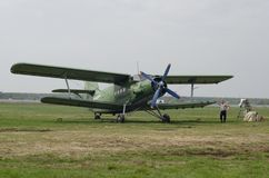 Homme avec le biplan vert AN2 d'avions sur la piste verte photo stock