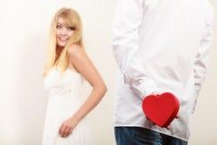 Homme avec le boîte-cadeau en forme de coeur pour la femme Images stock