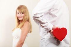Homme avec le boîte-cadeau en forme de coeur pour la femme Photo stock