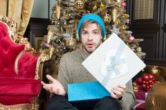 Homme avec le boîte-cadeau ouvert étonné de visage à l'arbre de Noël Photo stock