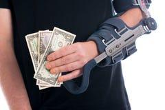 Homme avec le bras cassé montrant des dollars Photos stock