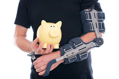 Homme avec le bras cassé montrant la tirelire Image stock