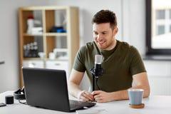 Homme avec le bureau d'ordinateur portable et de microphone ? la maison images stock