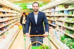 Homme avec le caddie dans l'hypermarché Image libre de droits