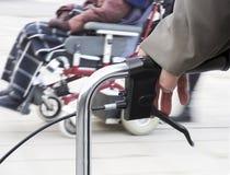 Homme avec le cadre et le fauteuil roulant de marche Image stock