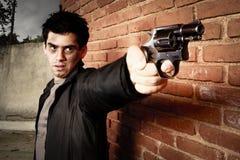 Homme avec le canon dans une ruelle Photographie stock libre de droits