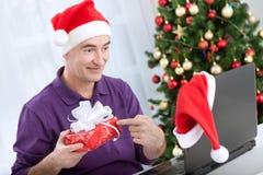 Homme avec le chapeau de Santa parlant avec l'ami et tenant le cadeau Image stock