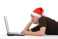 Homme avec le chapeau et l'ordinateur portatif de Noël Photo stock