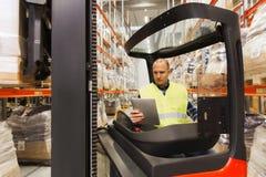 Homme avec le chariot élévateur fonctionnant de PC de comprimé à l'entrepôt Image stock