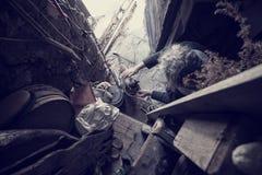 Homme avec le chat de alimentation de longs cheveux gris mal peignés par la porte dans vieux malpropre Photographie stock