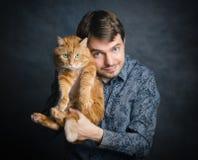 Homme avec le chat rouge Photographie stock